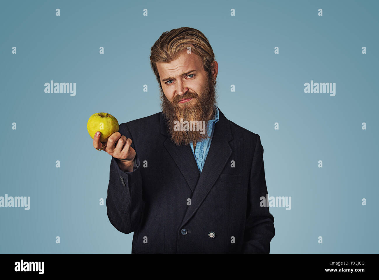 I am sick of these healthy diets. Closeup portrait unhappy young man nutritionist personal fitness trainer holding and offering an apple with skeptica - Stock Image