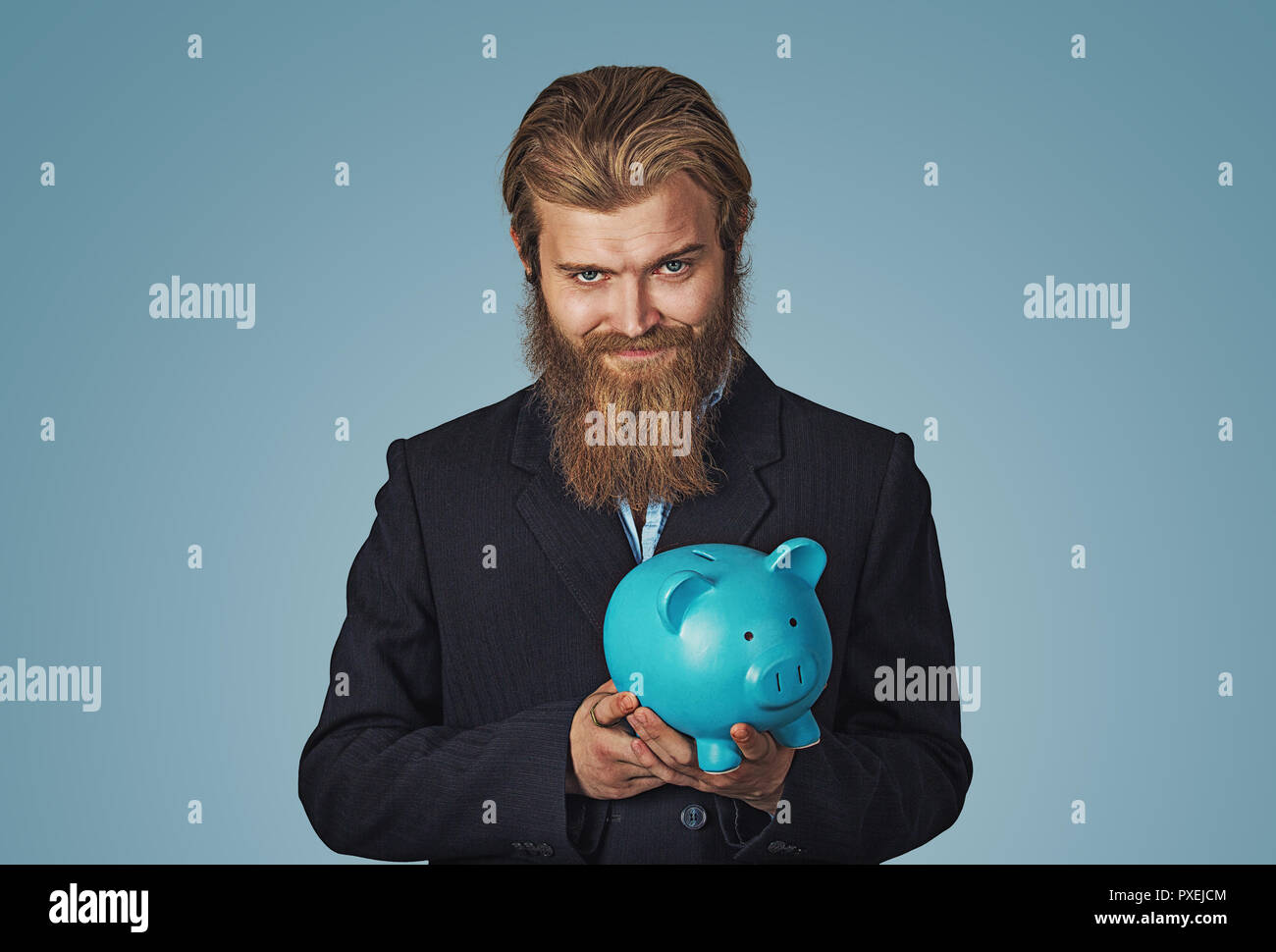 Sly Young man holding piggy bank plotting. Bearded hipster businessman Isolated on blue Background. Negative face expression, human emotion, body lang - Stock Image