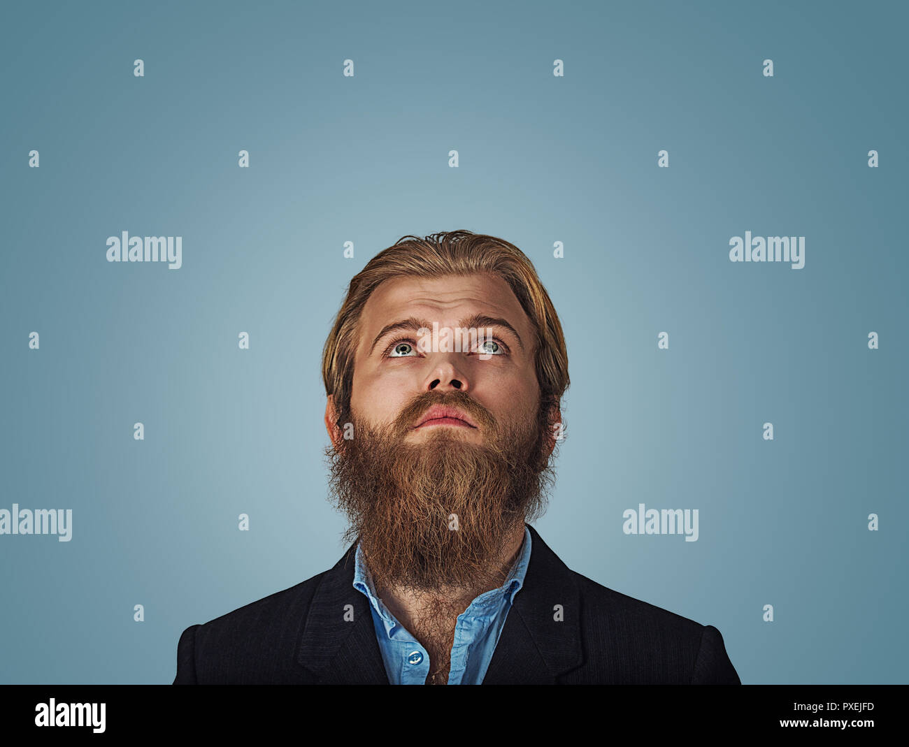 Head shot confused serious hipster business man thinking looking up thoughtful isolated on gray grey wall background with copy space above head. Human - Stock Image