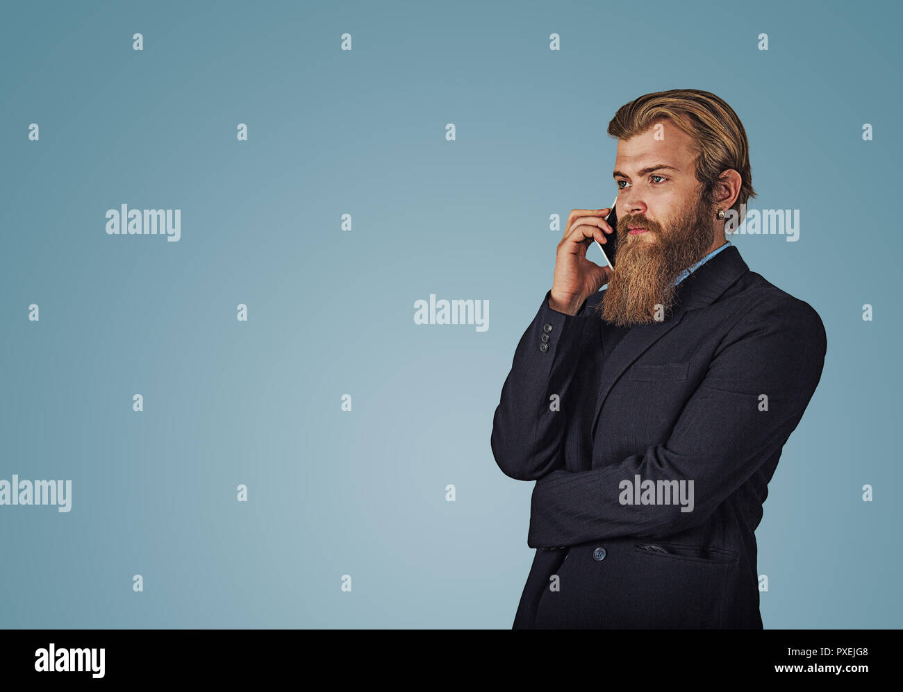 Bearded hipster business man holding talking by mobile phone isolated on blue studio wall Background. Serious face expression, human emotion, body lan Stock Photo