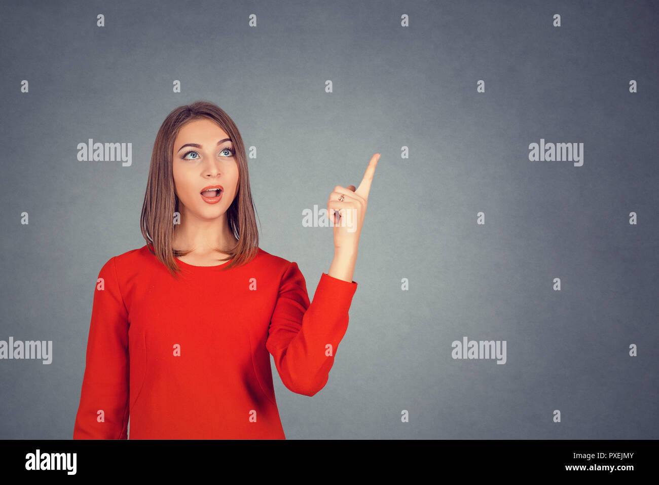 Surprised woman pointing her finger up - Stock Image