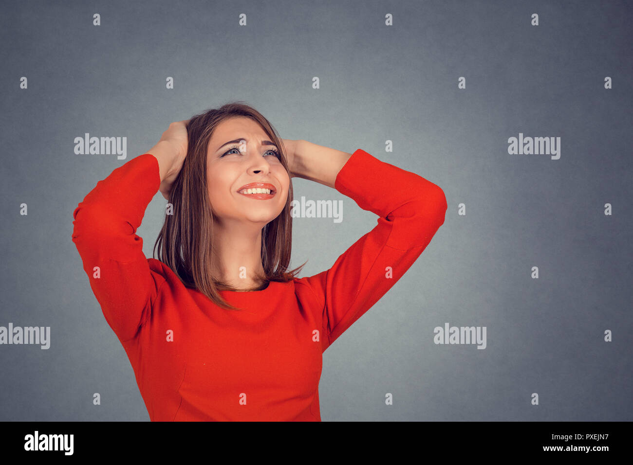 angry woman covering ears looking up stop loud noise - Stock Image