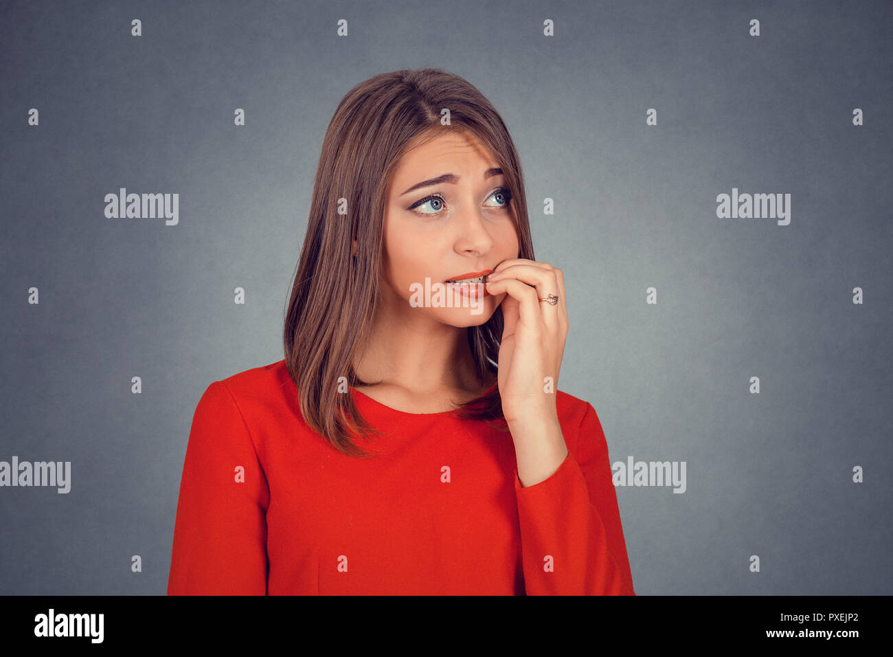 nervous looking woman biting her fingernails craving something - Stock Image