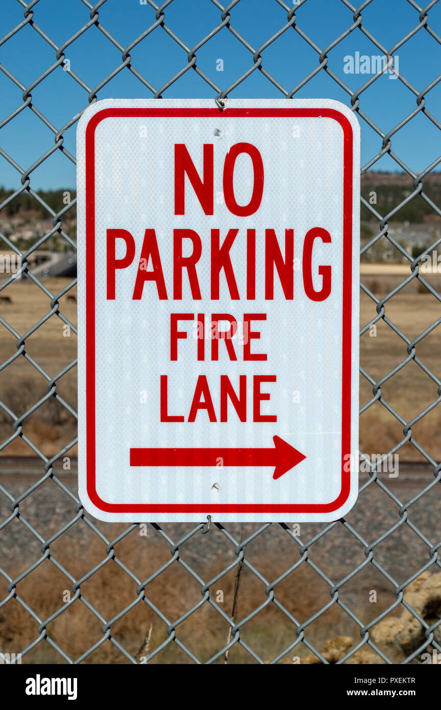 No parking fire lane sign on fence in parking lotStock Photo