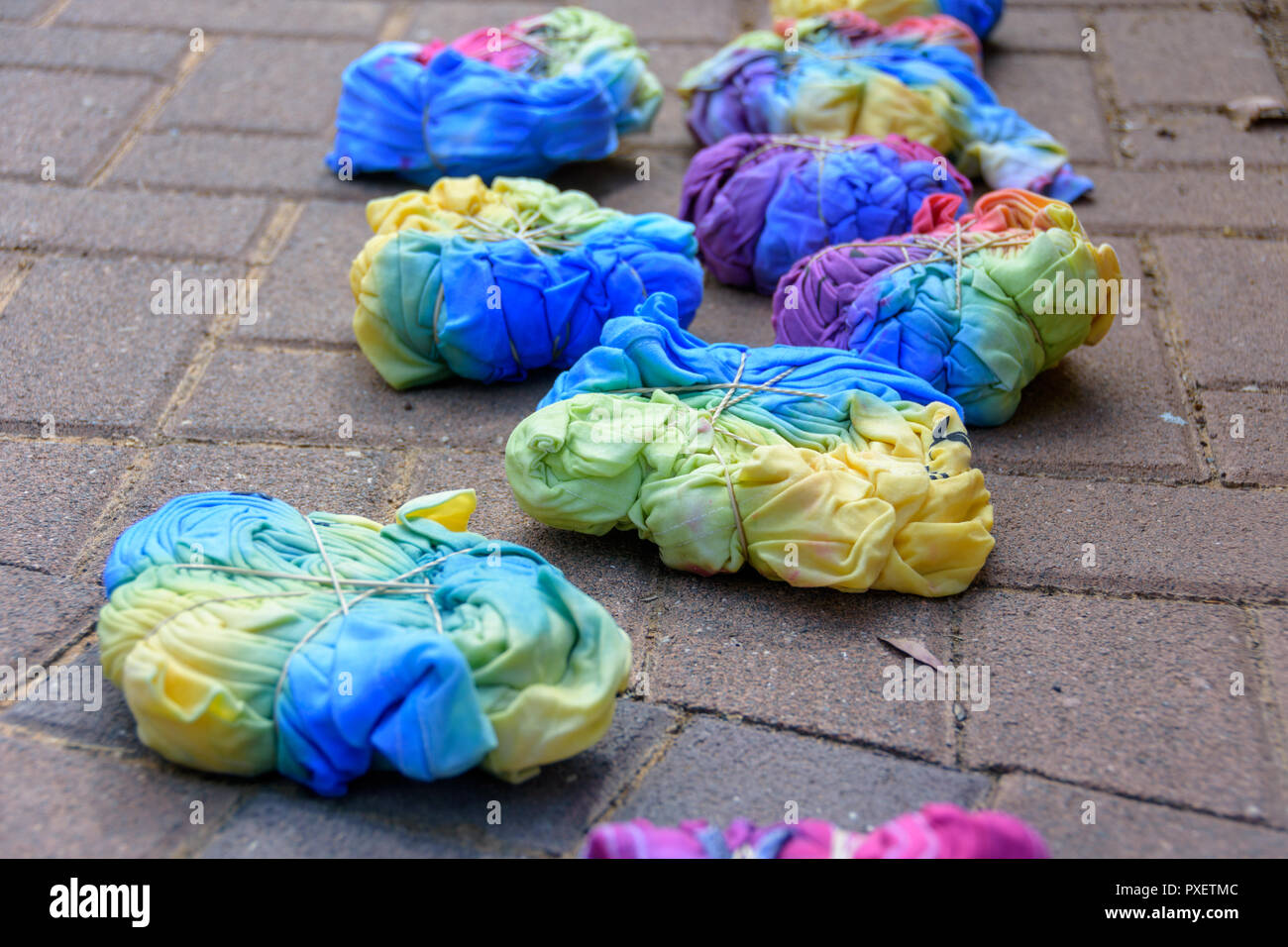 b7639759f9c2d3 Still-wet tie-dye T-shirts compressed with rubber bands after being painted