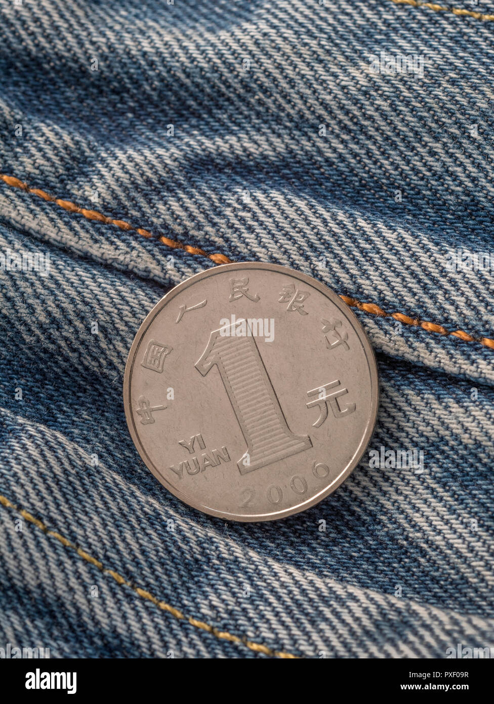 Chinese Yuan / Renminbi coin with pocket - metaphor for personal earnings, Chinese wages, wage levels. - Stock Image