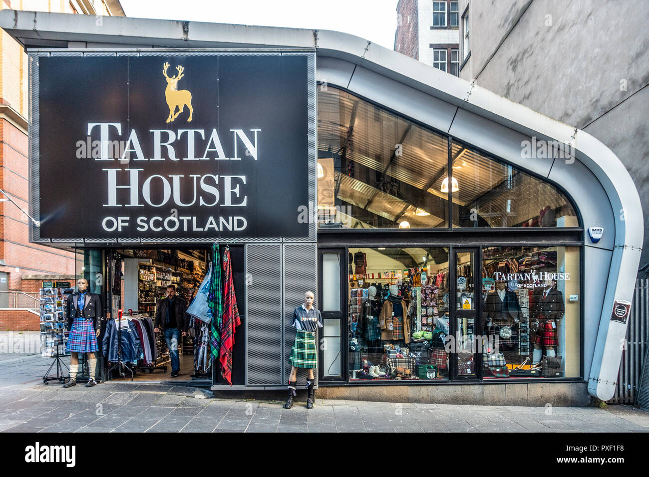 Customer leaving the main entrance of the Tartan House of Scotland shop, a Scottish souvenir shop, in Buchanan Street, Glasgow, Scotland, UK - Stock Image