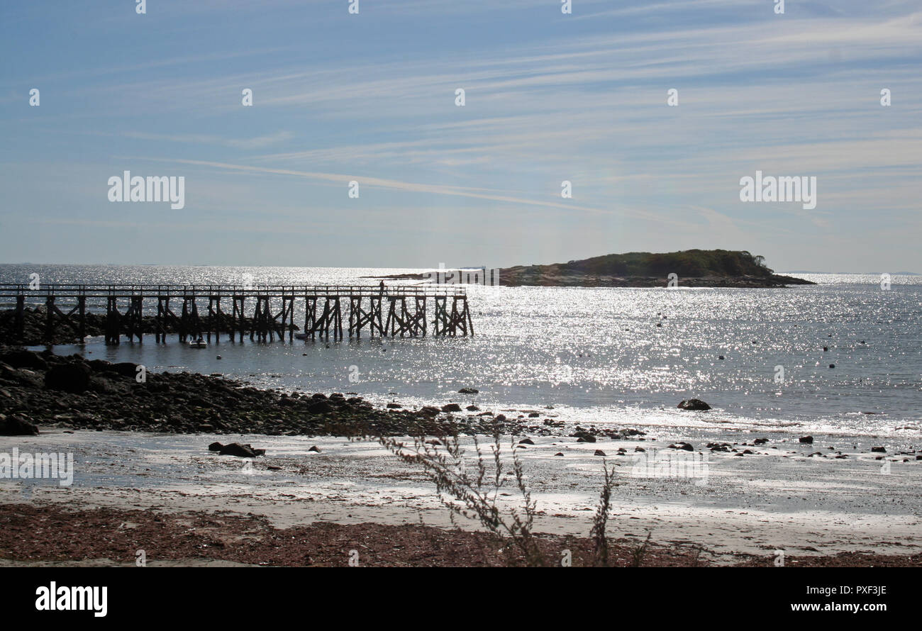 Magnolia pier on Gloucester's Massachusetts southernmost harbor since early 1800's highlighted by the sparkling ocean, glistening beach and blue sky. - Stock Image