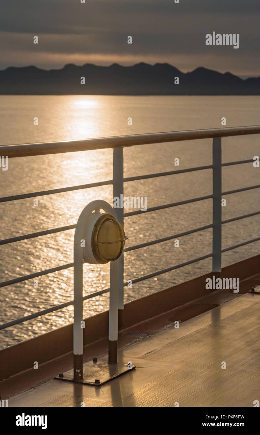 Nautical cruise ship deck walkway metal and brass exterior marine light fixture, port side of ship. - Stock Image