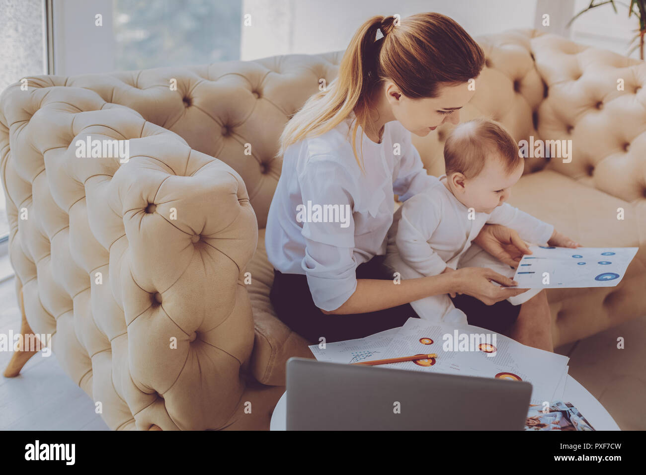 Corporate remote worker feeling engaged in new project while nursing her child - Stock Image