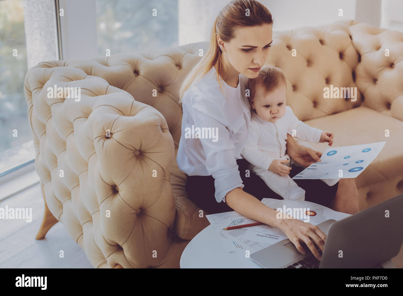Career woman typing business letter while spending time with little daughter - Stock Image