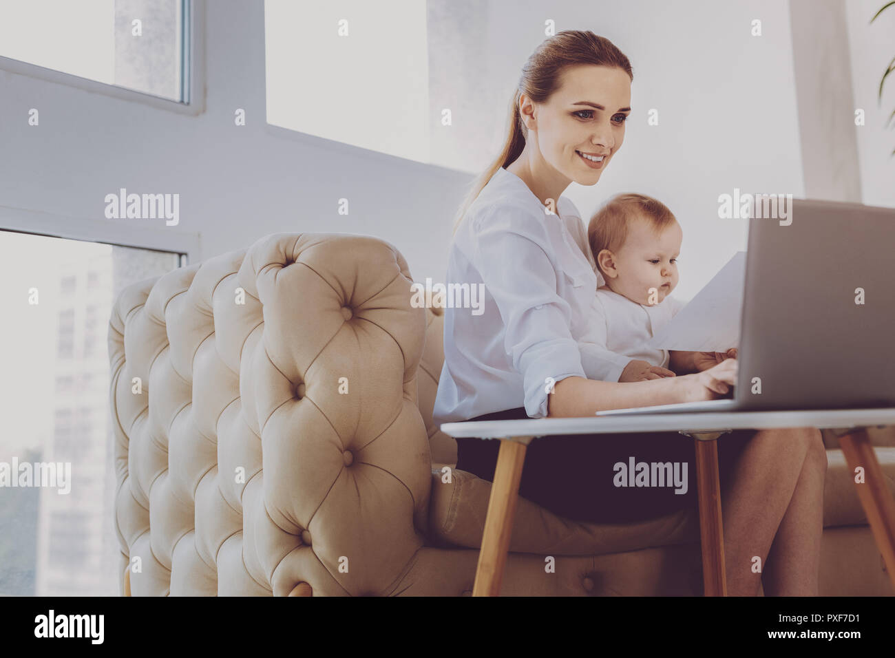 Prosperous sales manager feeling involved in distracting her newborn baby - Stock Image