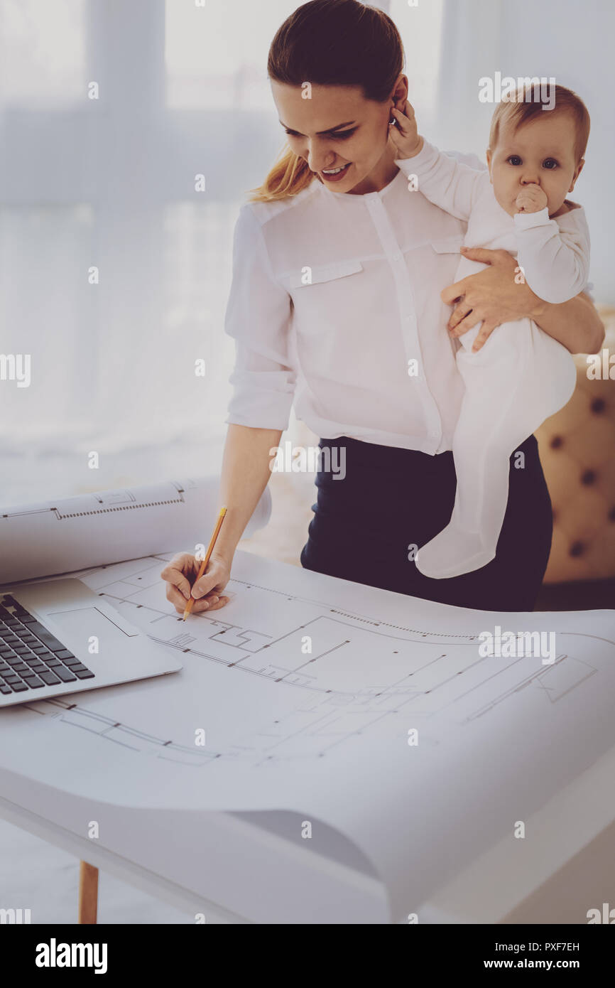 Working successful mother engineering serious project while holding cute baby - Stock Image