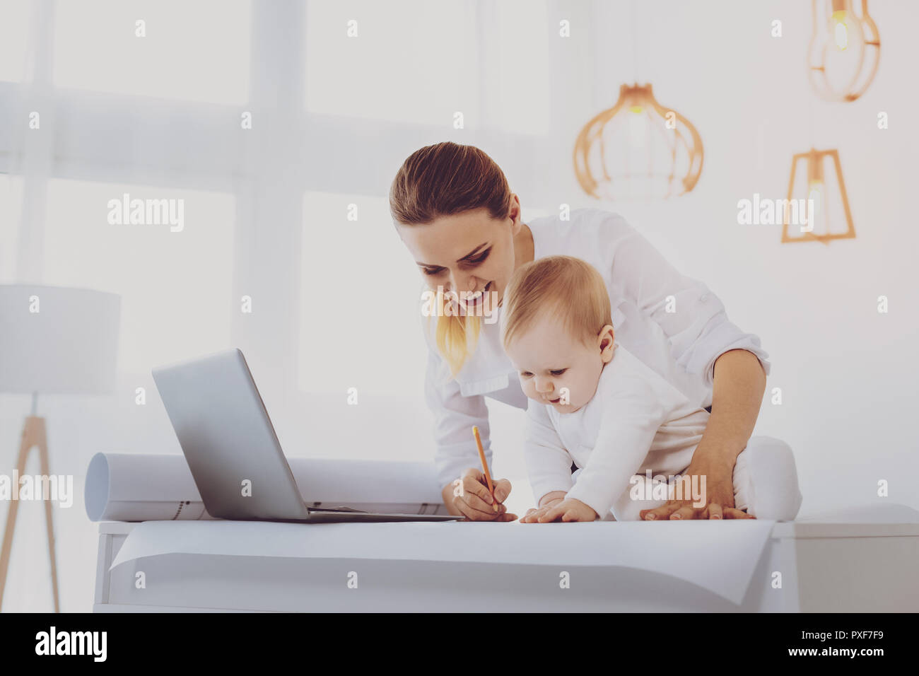 Young remote journalist writing letter while spending free time with toddler - Stock Image