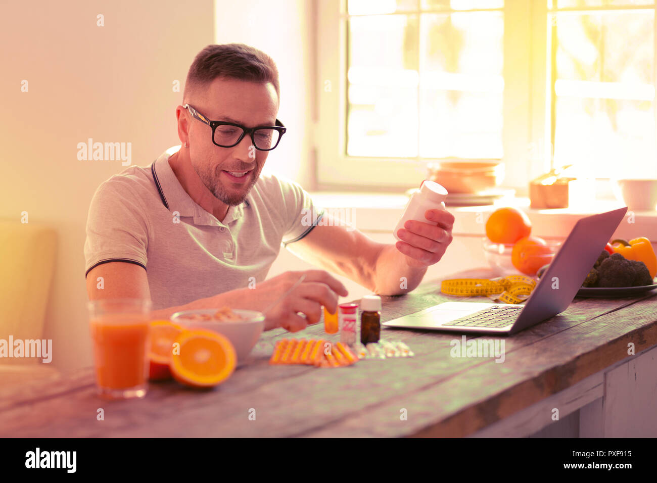 Smiling man reading a prescription of different pills - Stock Image