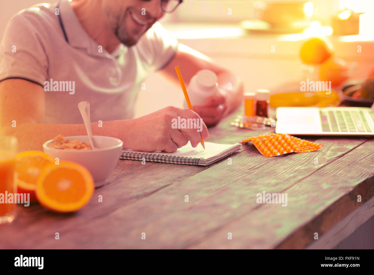 Smiling nice man making different notes in the notebook - Stock Image
