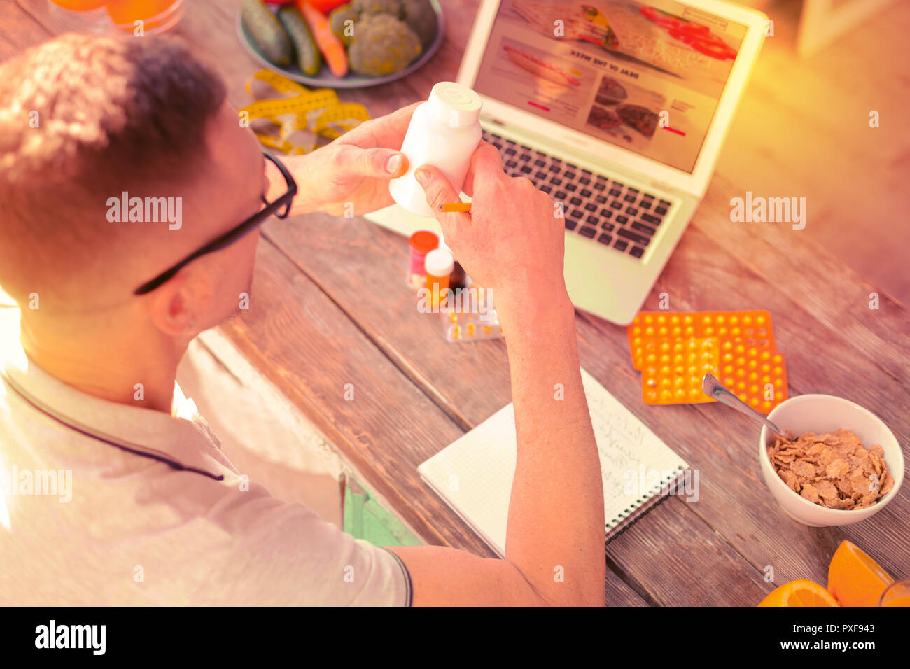 Curious pleasant man checking different medicine on the Internet - Stock Image