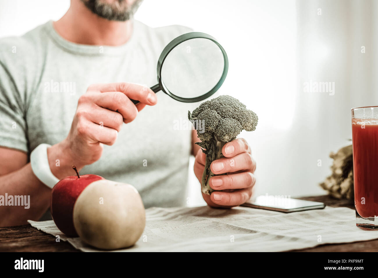 Nice pleasant adult man using magnifying glass - Stock Image