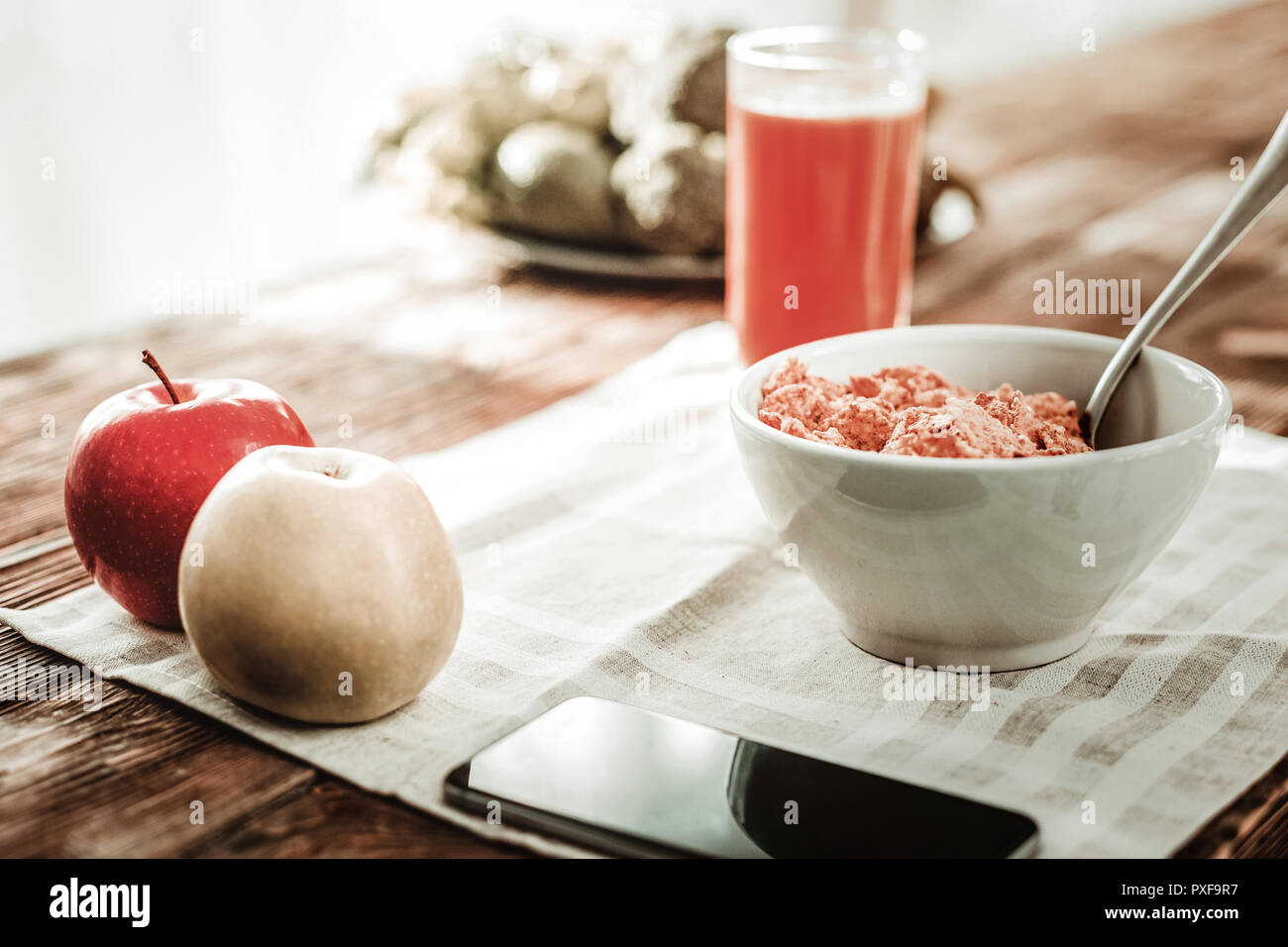 Close up of a smartphone lying near the bowl with cereal - Stock Image