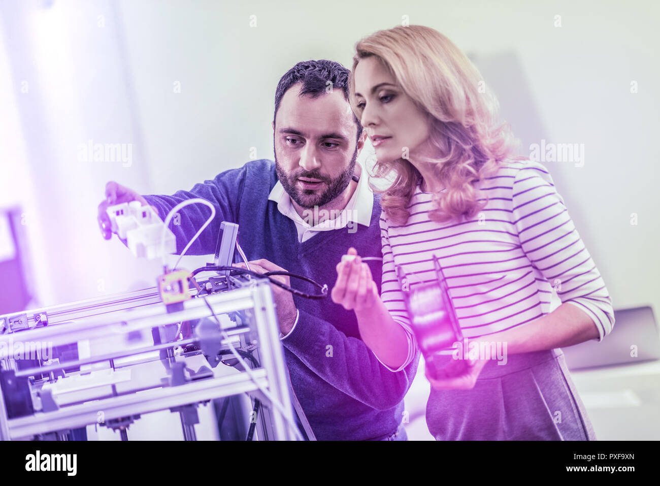 Bearded dark-haired man showing his colleague the way of using laser printer - Stock Image