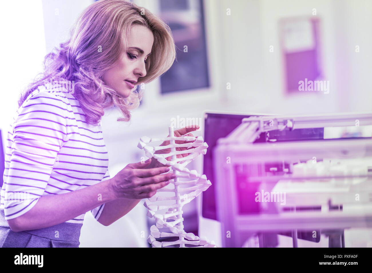 Blonde-haired experienced chemist looking at the model of molecular chain - Stock Image