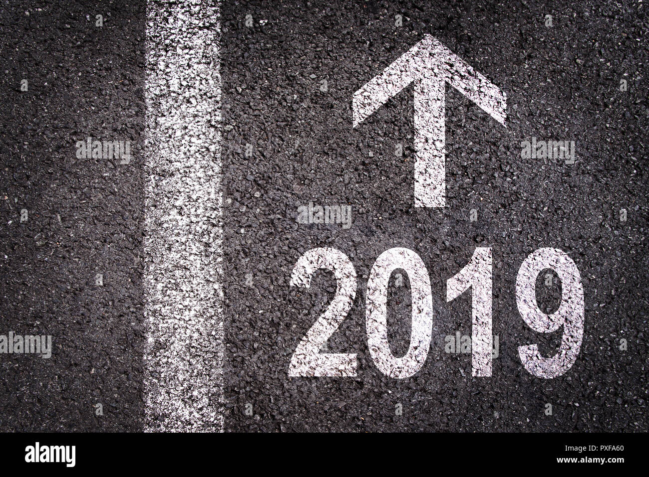 2019 and an arrow written on an asphalt road background - Stock Image