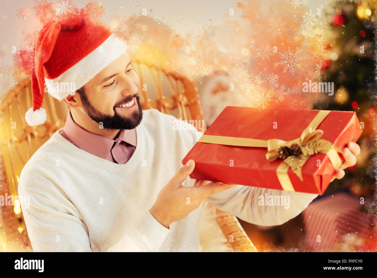 Generous kind-hearted boyfriend holding nice big Christmas gift box for his wife - Stock Image