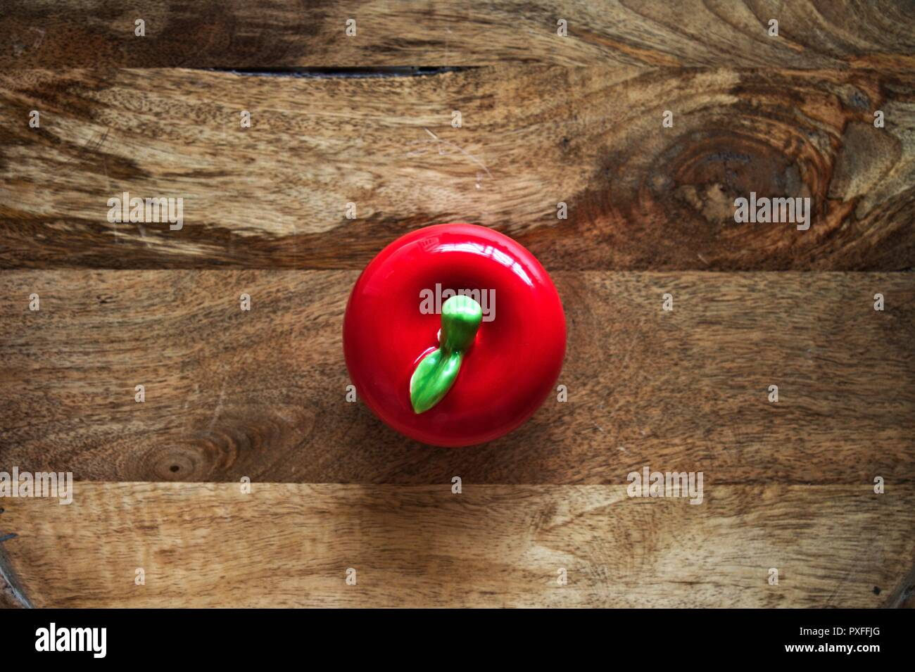 Red, round ceramic apple,flat lay, against wooden board background. Stock Photo