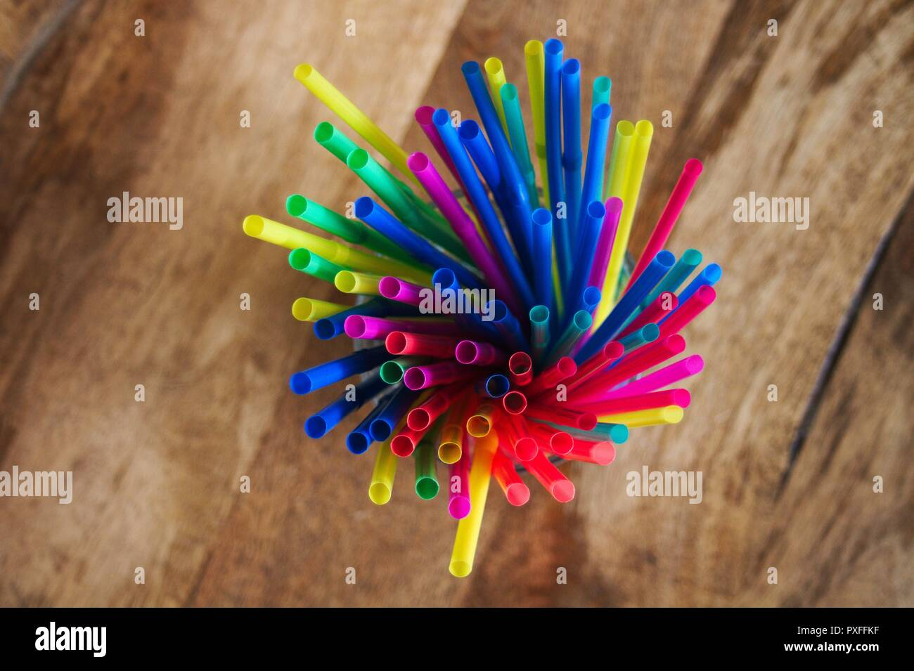 A collection of new plastic, disposable colored straws standing upright in a cup. Stock Photo
