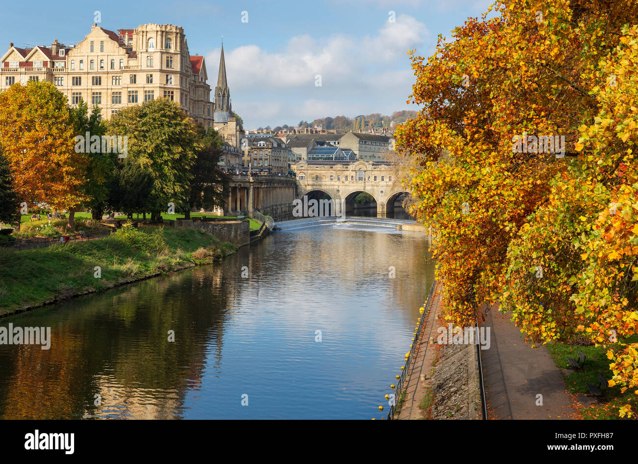 The famous landmarks of Pulteney Weir and Pulteney Bridge surrounded by vibrant autumnal trees on the River Avon in Bath, UK. - Stock Image