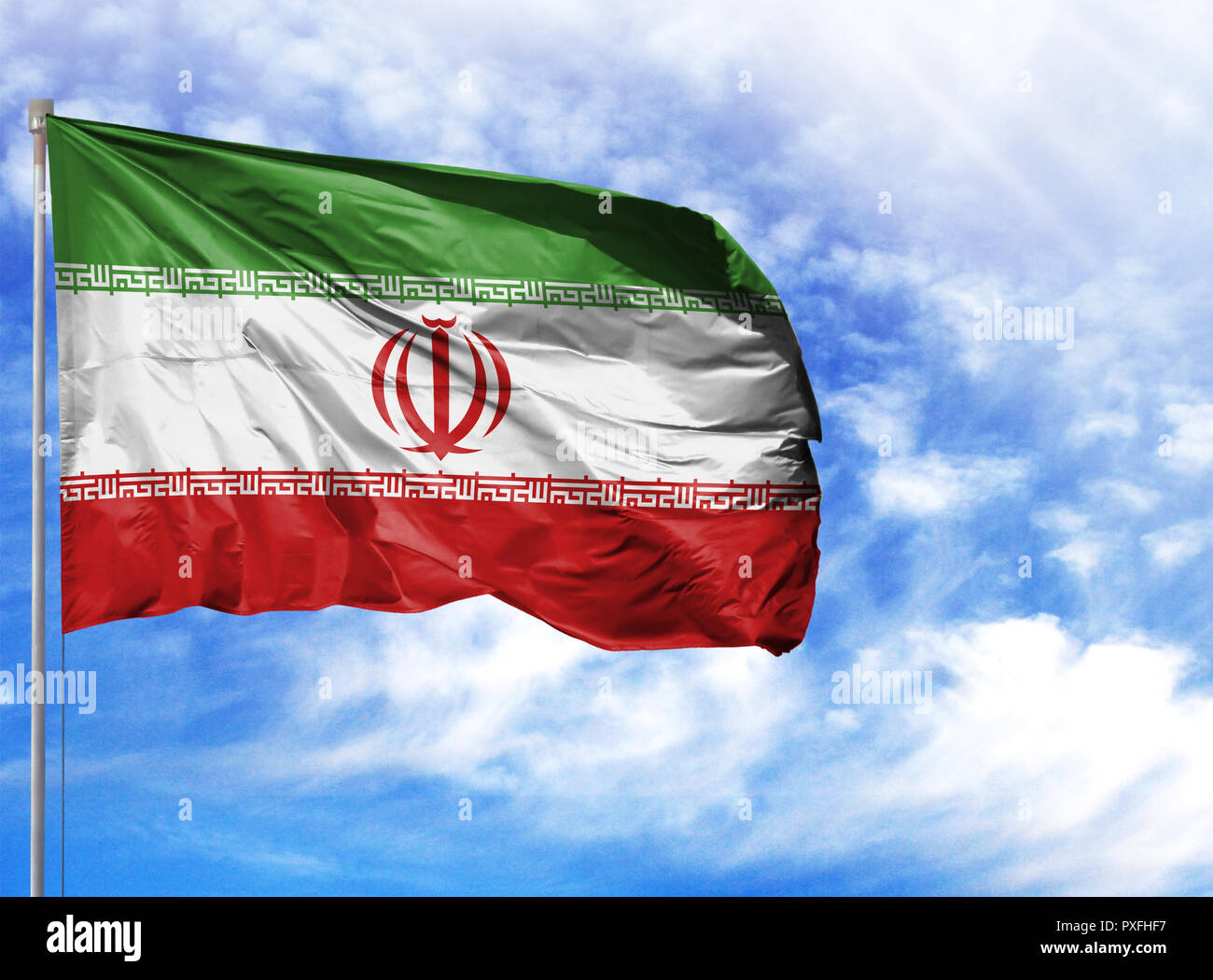 National flag of Iran on a flagpole in front of blue sky. - Stock Image