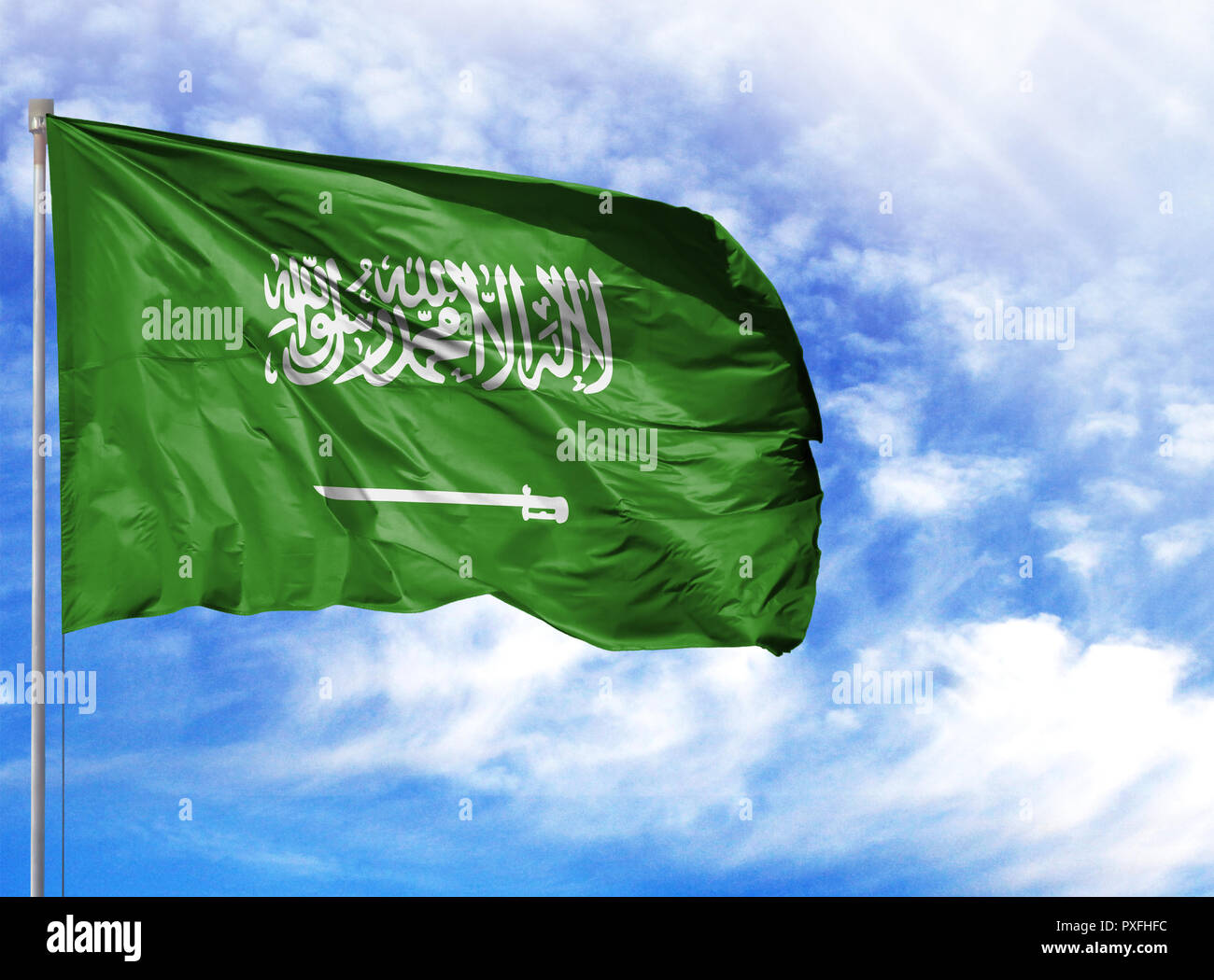 National flag of Saudi Arabia on a flagpole in front of blue sky. - Stock Image