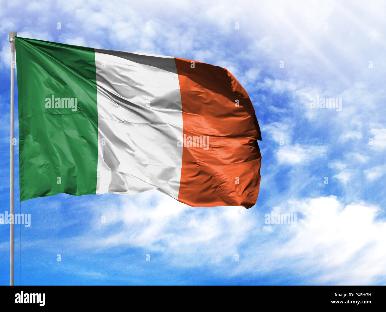 National flag of Ireland on a flagpole in front of blue sky. - Stock Image