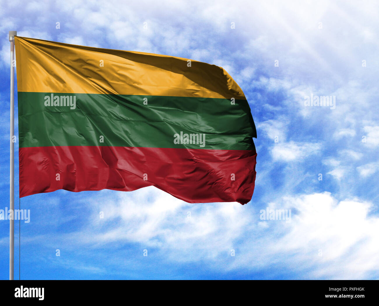 National flag of Lithuania on a flagpole in front of blue sky. - Stock Image