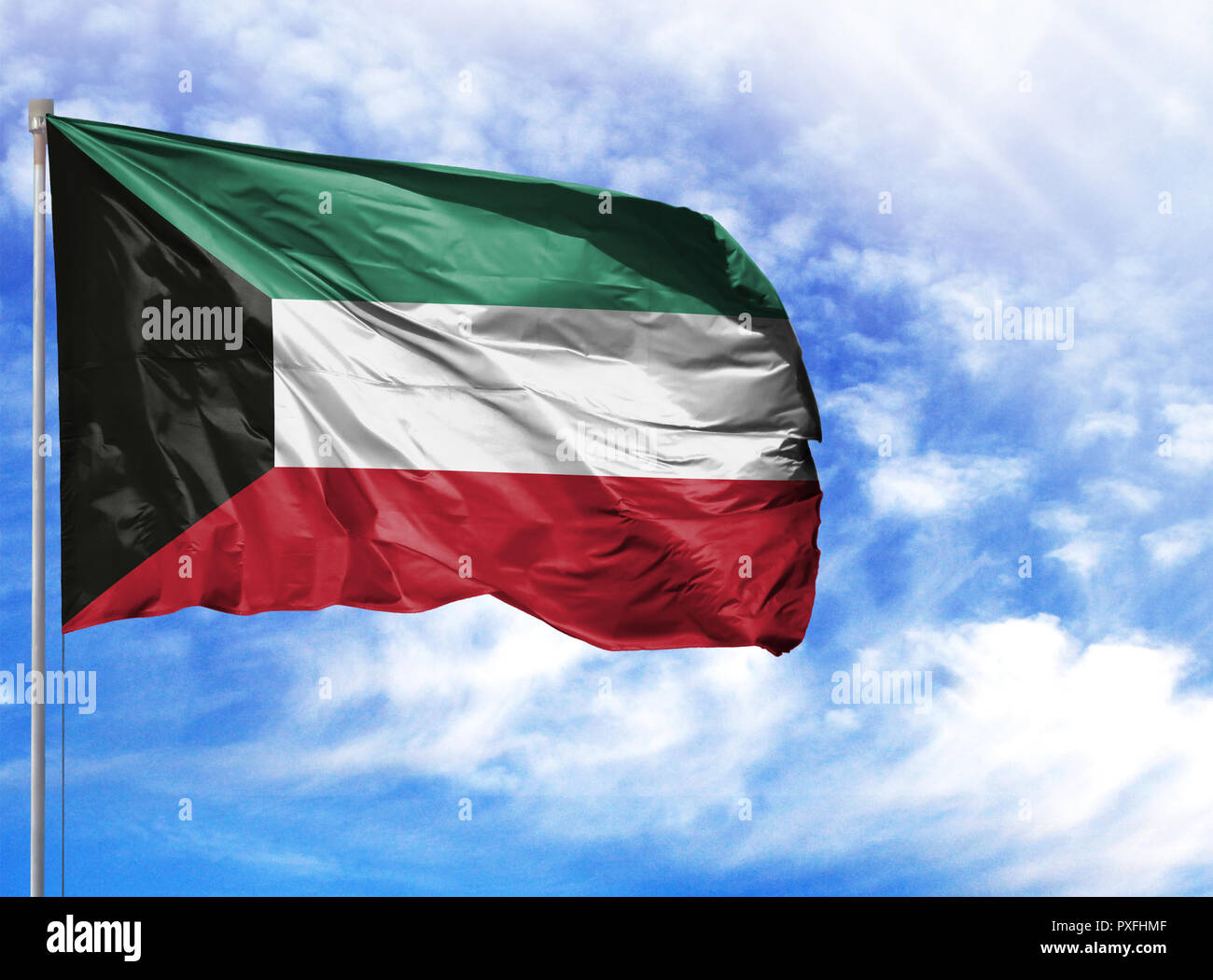 National flag of Kuwait on a flagpole in front of blue sky. Stock Photo