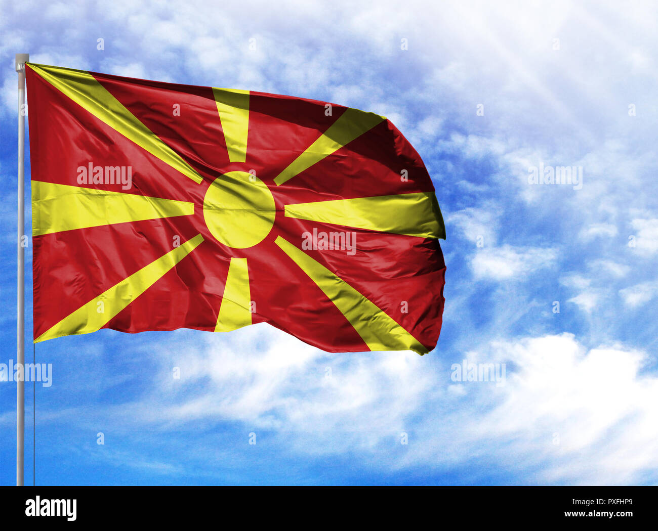 National flag of Macedonia on a flagpole in front of blue sky. - Stock Image