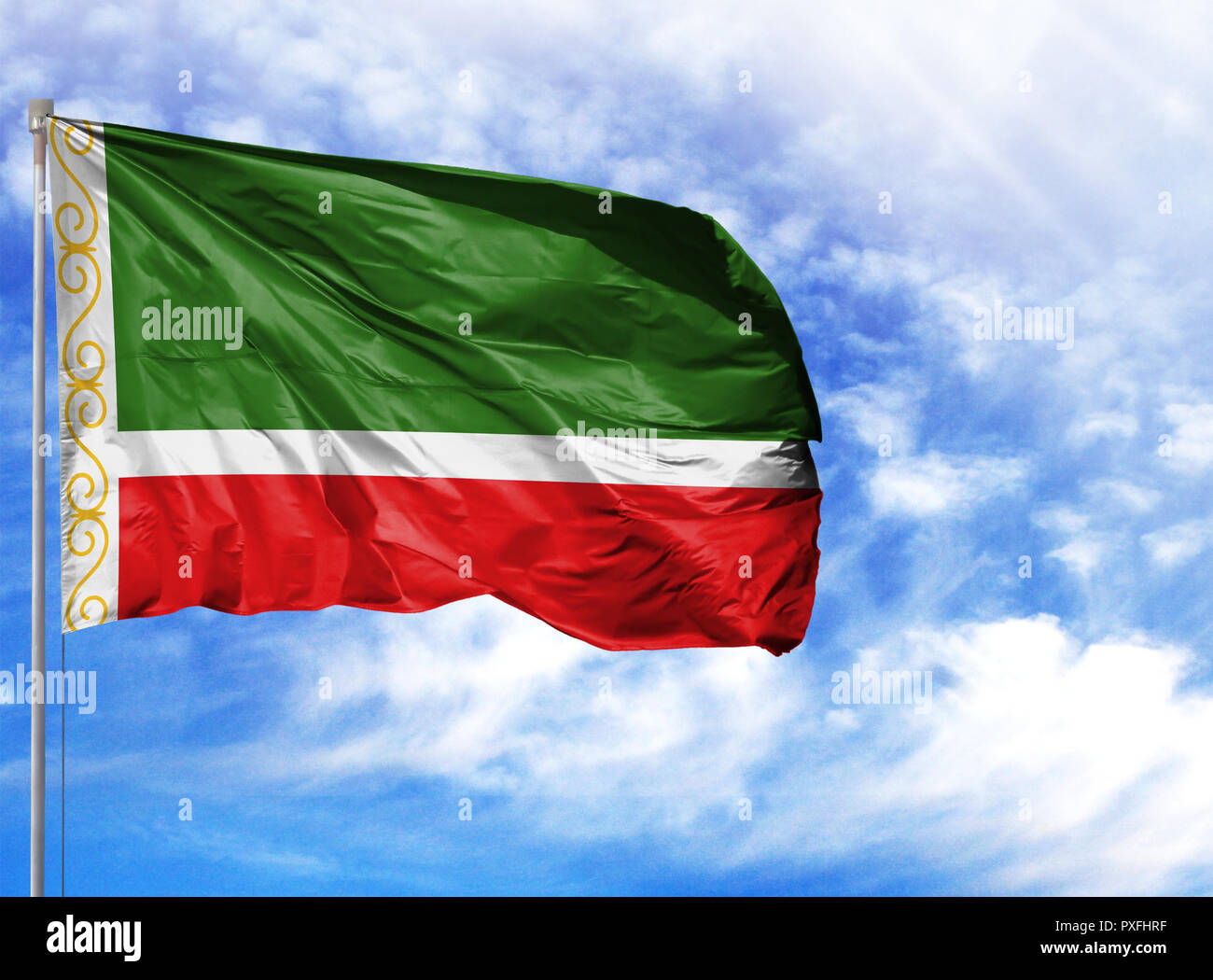 National flag of Chechen Republic on a flagpole in front of blue sky. - Stock Image