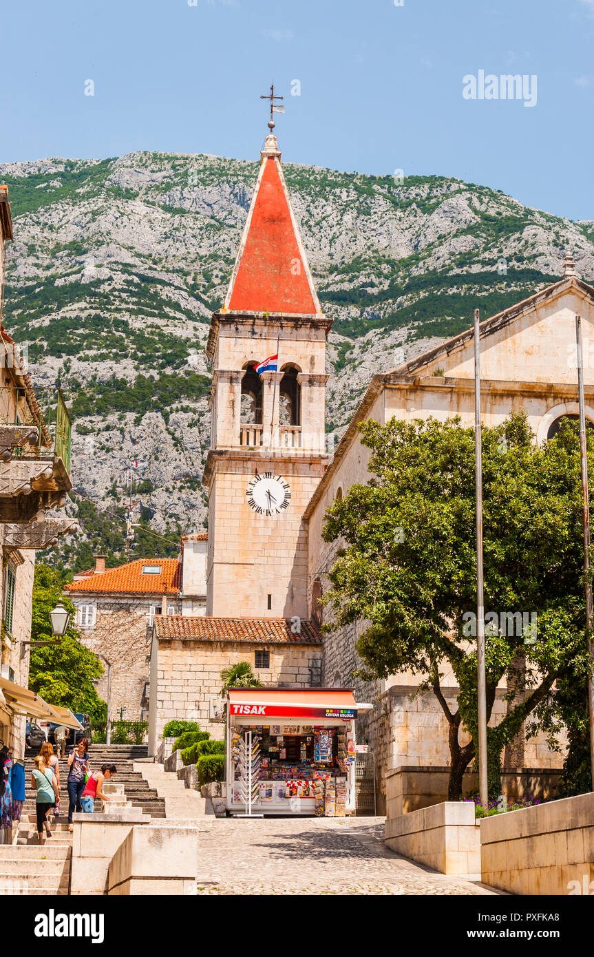 Makarska, Сroatia - June 23, 2014: Cozy and vibrant medieval Old Town street of Makarska. Tourists and local people walking by the streets. Stock Photo
