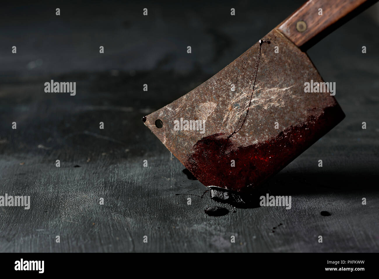 closeup of an old and rusty meat cleaver full of blood, stuck on a dark green rustic surface - Stock Image