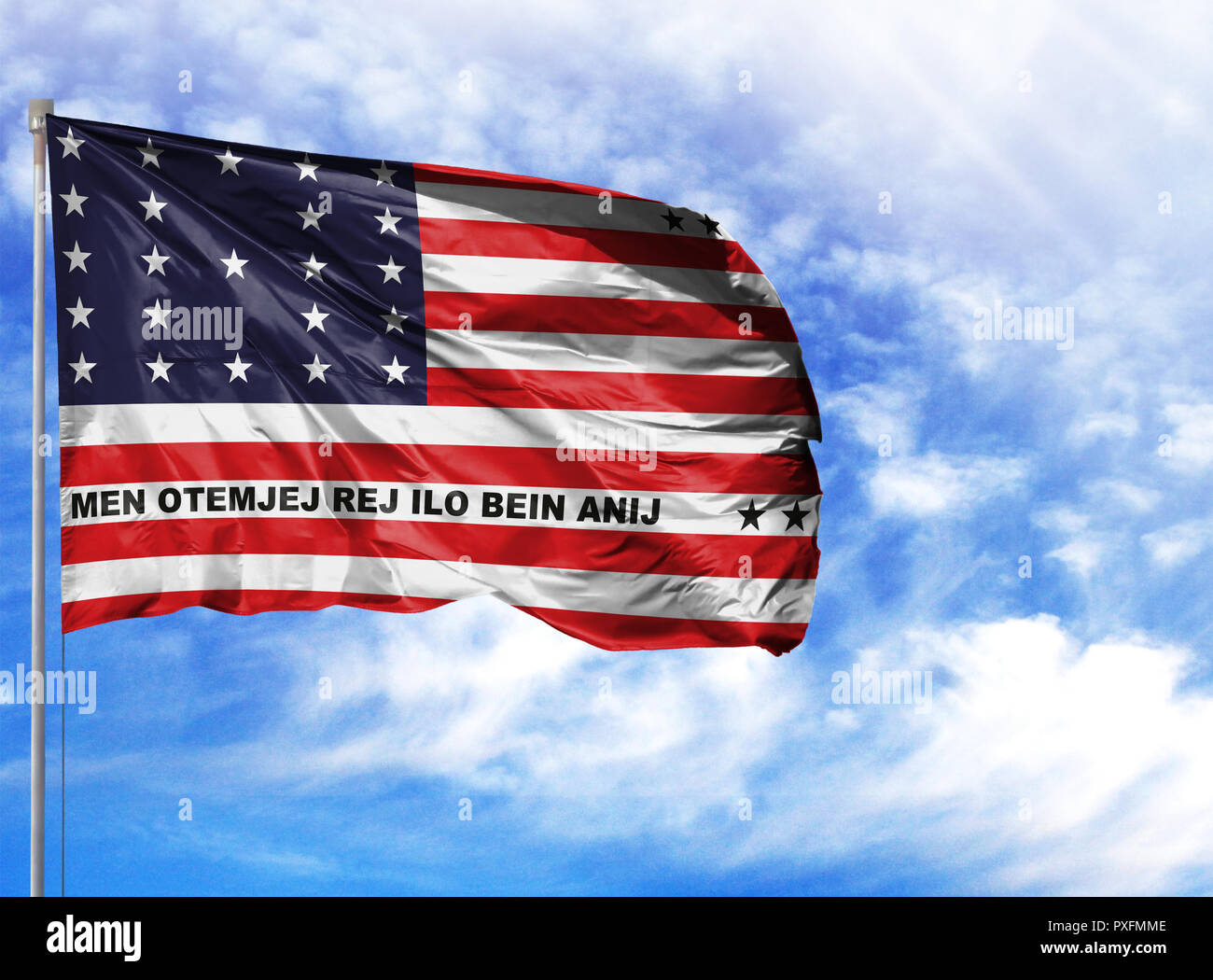 National flag of Bikini Atoll on a flagpole in front of blue sky. - Stock Image