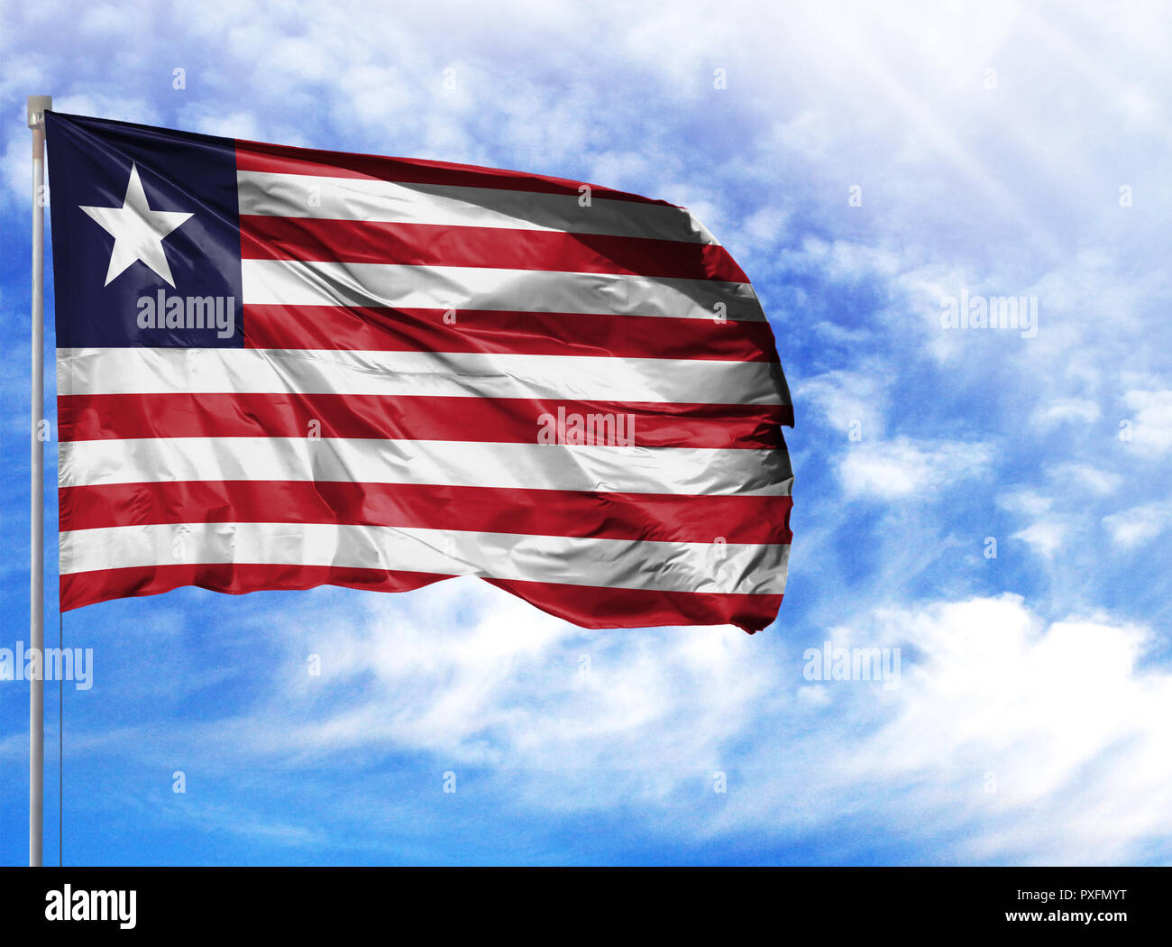 National flag of Liberia on a flagpole in front of blue sky. - Stock Image