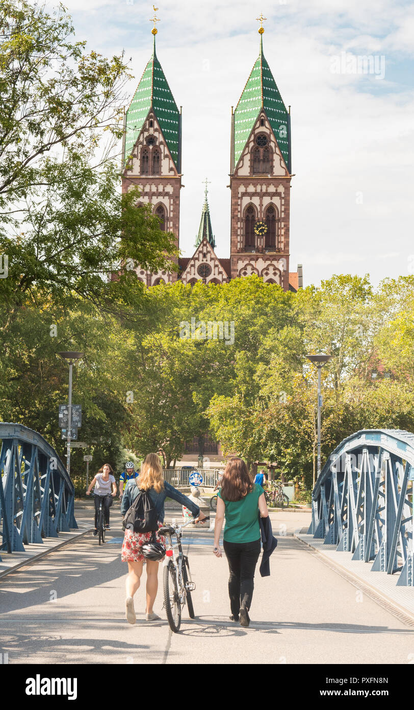 young women on bridge walking towards the Sacred Heart Church and Stuhlinger church square in Freiburg im Breisgau, Germany, Europe - Stock Image