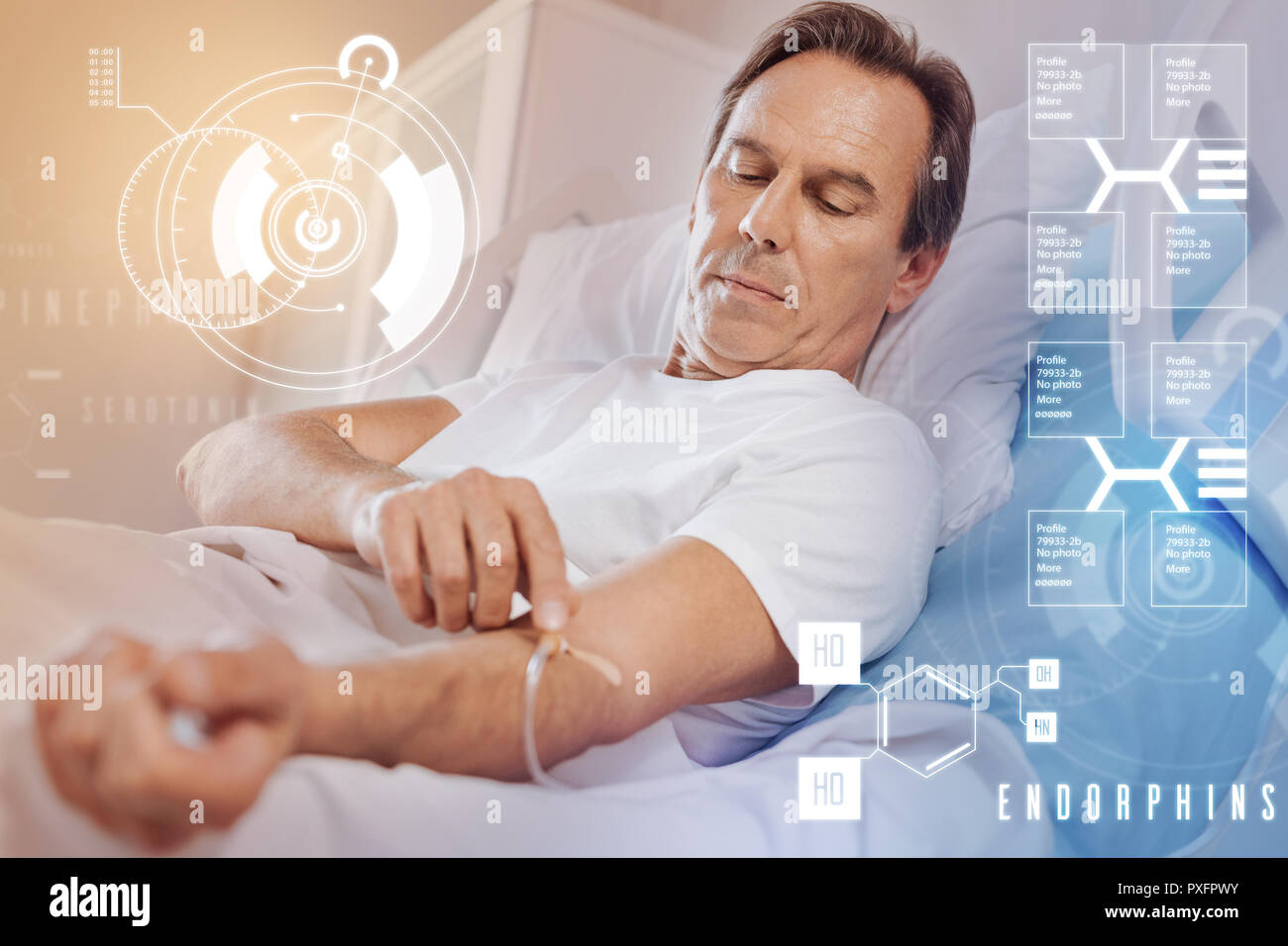 Serious patient staying in bed and feeling worried while touching his catheter - Stock Image