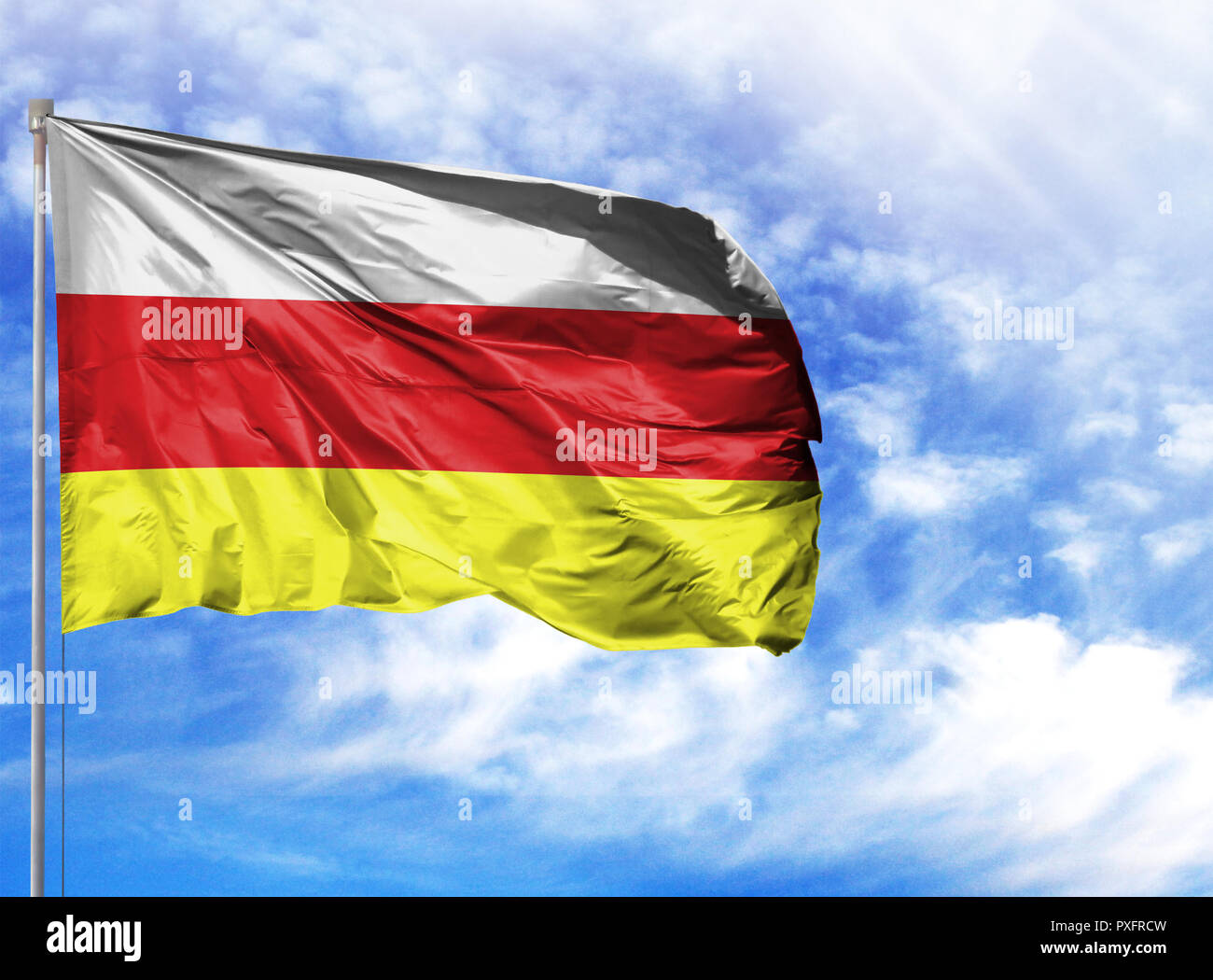National flag of South Ossetia on a flagpole in front of blue sky. - Stock Image