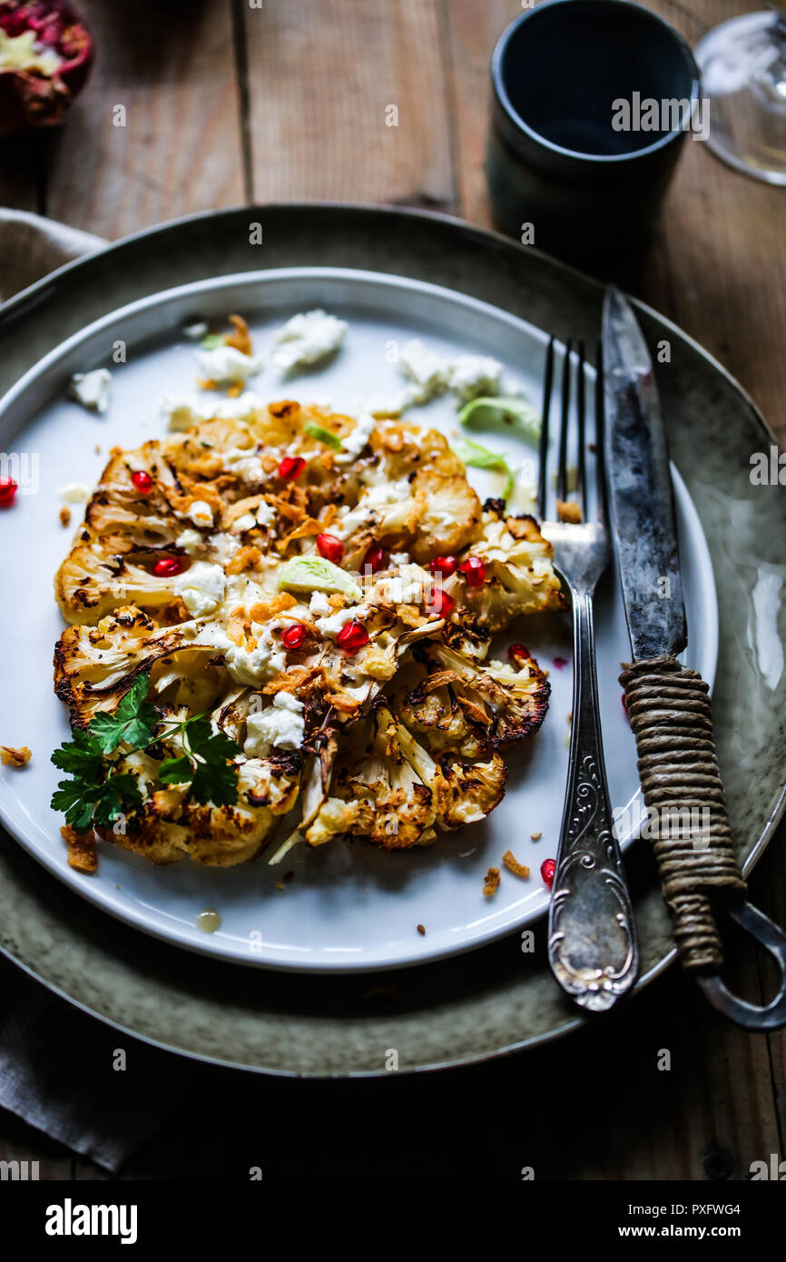 Roasted cauliflower steak with tahini sauce, feta cheese and pomegranate. - Stock Image