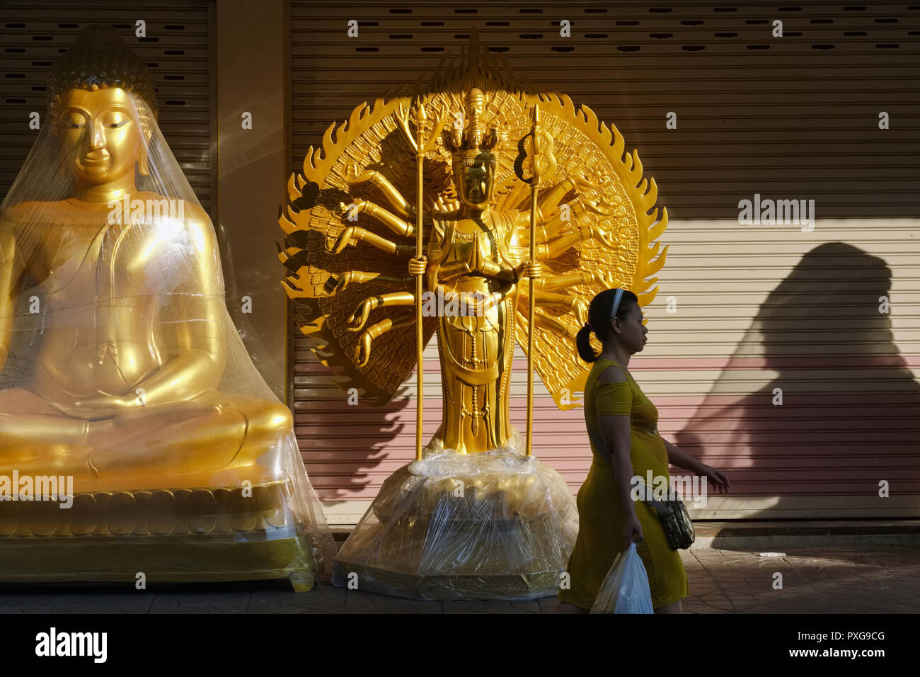 A woman, on an early morning, walking past Buddhist statues placed outside a shop for Buddhist artifacts, Bamrung Muang Rd., Bangkok, Thailand - Stock Image