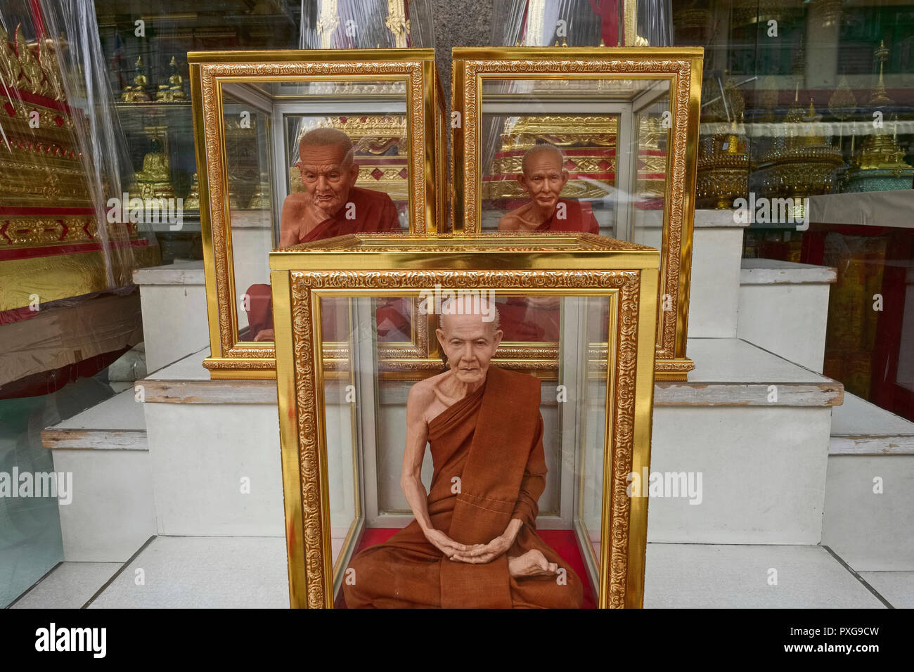 Fibre glass miniatures of revered Thai monks - or Luang Pu - in gold-rimmed glass cases, on sale in Bamrung Muang Rd., Bangkok, Thailand - Stock Image