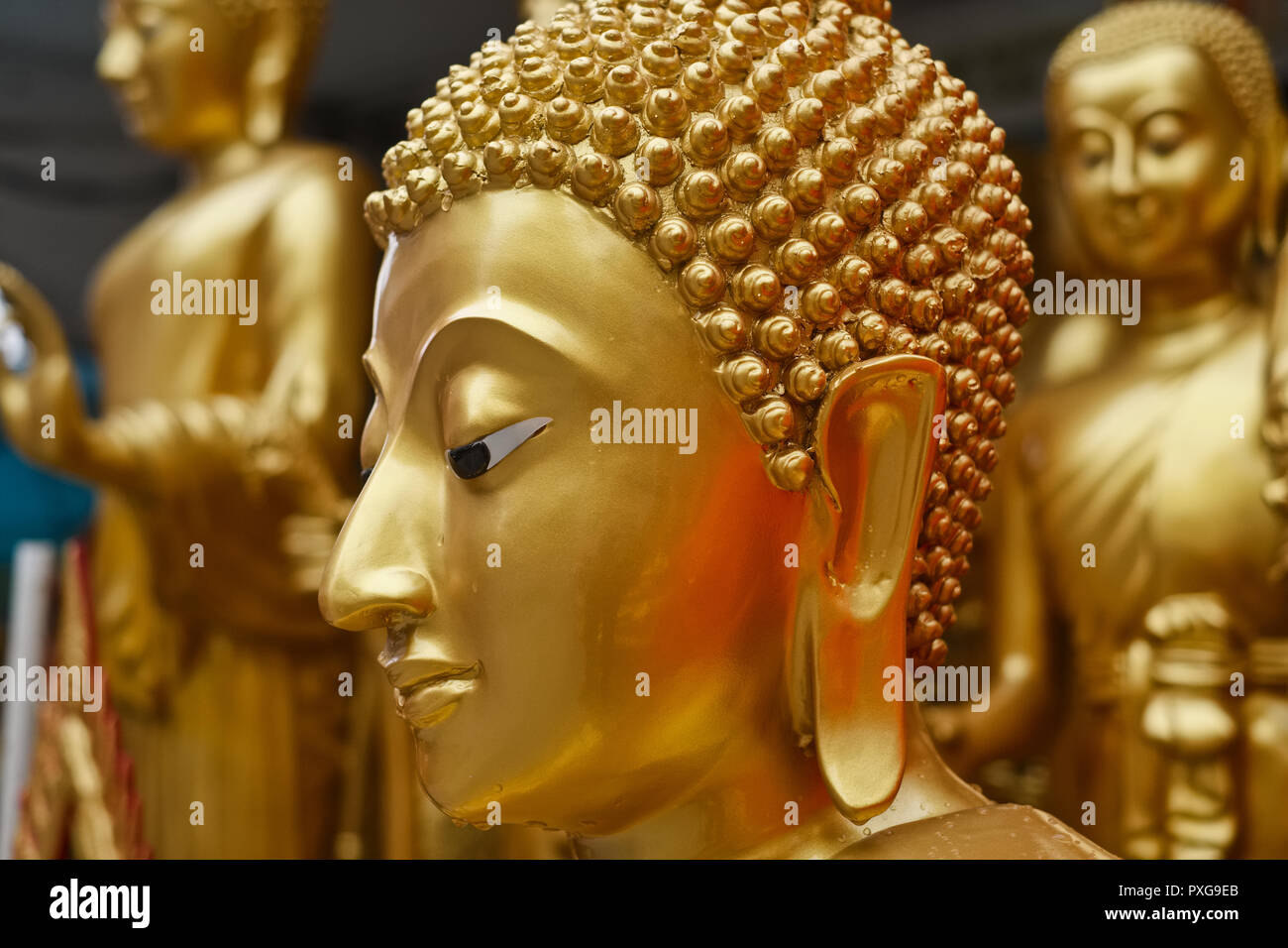 Outside a factory-shop for Buddhist artifacts in Bamrung Muang Rd., Bangkok, Thailand, Buddha statues wait to be transported for sale - Stock Image