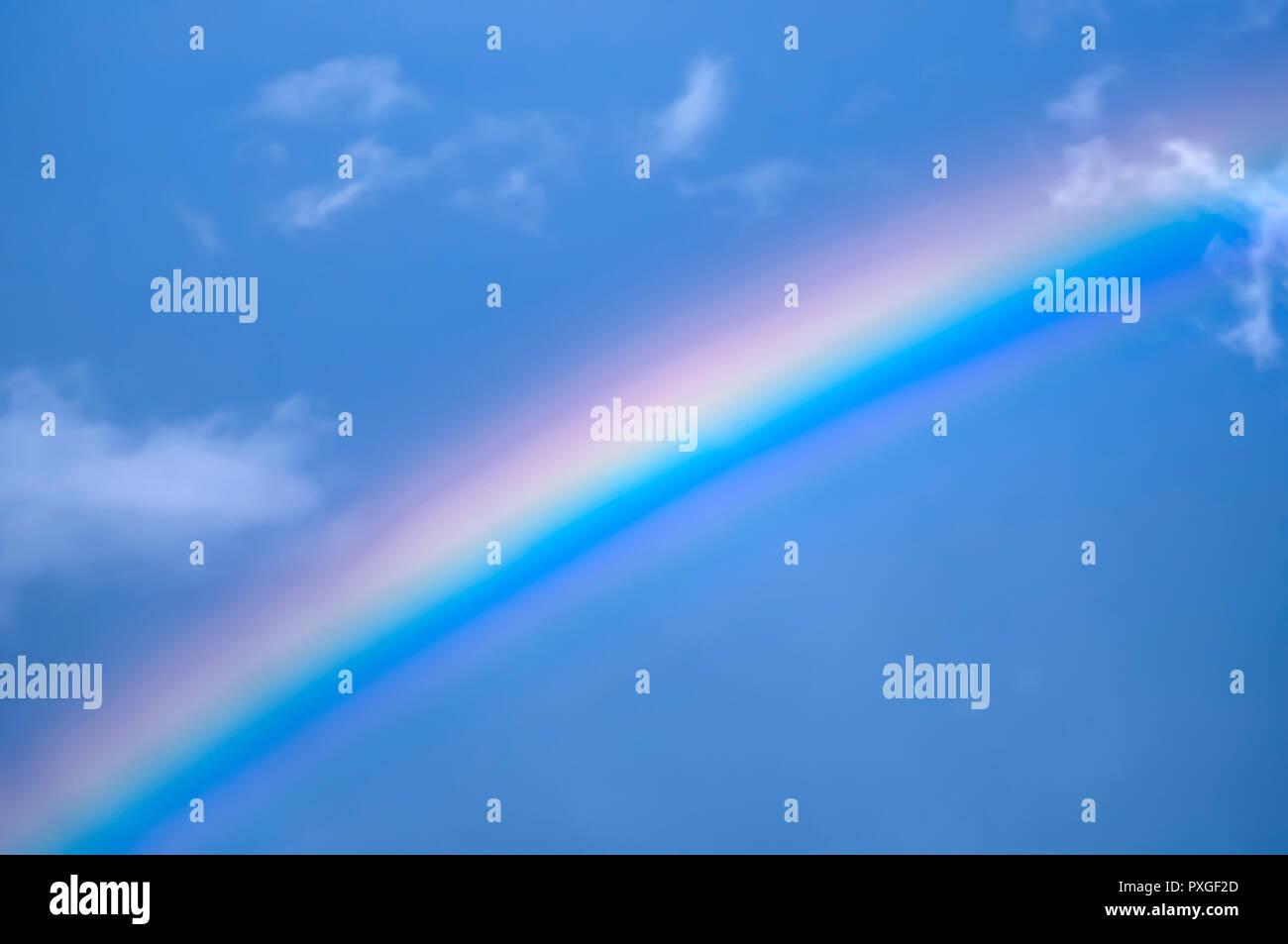 Rainbow on blue sky background - Stock Image