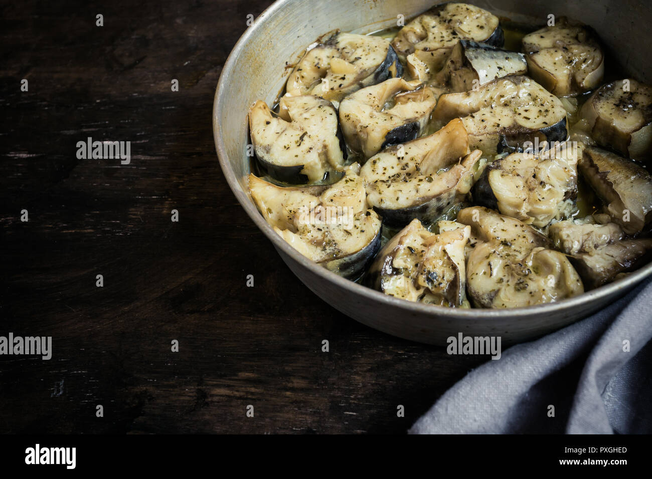 Baked fish mackerel in a pan, on a wooden background. Slices of baked Atlantic mackerel/ - Stock Image